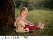 Купить «Маленькая девочка читает книгу в саду», фото № 28644763, снято 18 июня 2018 г. (c) Julia Shepeleva / Фотобанк Лори