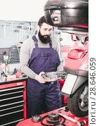 Купить «Positive male worker fixing failed scooter», фото № 28646059, снято 14 августа 2018 г. (c) Яков Филимонов / Фотобанк Лори