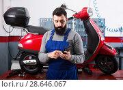 Купить «Worker counting sum for his repairing motorcycle», фото № 28646067, снято 14 августа 2018 г. (c) Яков Филимонов / Фотобанк Лори