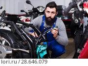 Купить «Smiling man worker fixing failed motorcycle», фото № 28646079, снято 25 сентября 2018 г. (c) Яков Филимонов / Фотобанк Лори