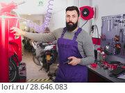 Купить «Positive male worker repairing motorbike», фото № 28646083, снято 15 августа 2018 г. (c) Яков Филимонов / Фотобанк Лори