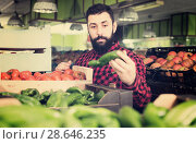 Купить «Young male seller offering sweet peppers in shop», фото № 28646235, снято 15 ноября 2016 г. (c) Яков Филимонов / Фотобанк Лори
