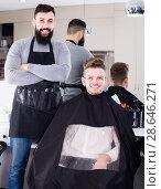 Купить «positive guy stylist demonstrating final haircut to client at hairdressing salon», фото № 28646271, снято 27 января 2017 г. (c) Яков Филимонов / Фотобанк Лори
