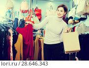 Купить «Cheerful female deciding on pretty blouse», фото № 28646343, снято 7 февраля 2017 г. (c) Яков Филимонов / Фотобанк Лори