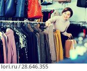 Купить «Happy woman choosing turtleneck sweater», фото № 28646355, снято 7 февраля 2017 г. (c) Яков Филимонов / Фотобанк Лори