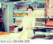 Купить «Seller showing white fabric», фото № 28646399, снято 4 января 2017 г. (c) Яков Филимонов / Фотобанк Лори