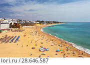 Купить «Portugal. Algarve. Top view of the beautiful sandy beaches near the old town of Albufeira and the silhouettes of people vacationing by the sea coast on a sunny day», фото № 28646587, снято 24 сентября 2012 г. (c) Виктория Катьянова / Фотобанк Лори