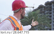 Купить «Man in a helmet, architect, engineer, manager tells about the progress of construction in evening stock footage video», видеоролик № 28647715, снято 23 июня 2018 г. (c) Юлия Машкова / Фотобанк Лори