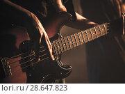 Купить «Guitarist plays on of bass guitar, close up», фото № 28647823, снято 11 декабря 2016 г. (c) EugeneSergeev / Фотобанк Лори