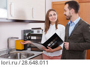 Young woman seller consulting man customer in shop of kitchen furnishing. Стоковое фото, фотограф Яков Филимонов / Фотобанк Лори