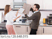 Купить «Salesman offering female client material for kitchen furniture», фото № 28648015, снято 11 апреля 2018 г. (c) Яков Филимонов / Фотобанк Лори