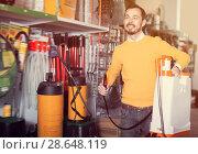 Купить «Positive guy deciding on best garden sprayer», фото № 28648119, снято 2 марта 2017 г. (c) Яков Филимонов / Фотобанк Лори