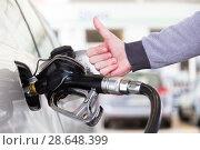 Купить «Petrol or gasoline being pumped into a motor vehicle car. Closeup of man, showing thumb up gesture, pumping gasoline fuel in car at gas station.», фото № 28648399, снято 30 апреля 2014 г. (c) Matej Kastelic / Фотобанк Лори