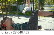 Купить «Young woman doing fitness exercises in front of muscular man pulled-up on the bar outdoors at sunny day», видеоролик № 28648435, снято 17 июля 2018 г. (c) Константин Шишкин / Фотобанк Лори
