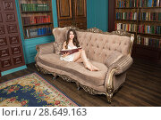 Купить «Young woman wearing chemise and peignoir sits on sofa in library and reads a book», фото № 28649163, снято 1 апреля 2018 г. (c) Сергей Дубров / Фотобанк Лори