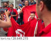 Купить «На Никольской улице в Москве футбольные фанаты знакомятся и фотографируются друг с другом. Девочка-россиянка фотографируется в тунисской красной шапке и с национальным флагом Туниса. Чемпионат мира по футболу FIFA 2018, Россия», фото № 28649215, снято 24 июня 2018 г. (c) Наталья Николаева / Фотобанк Лори