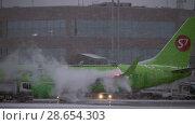 Купить «S7 Airlines aircraft being de-iced before the flight», видеоролик № 28654303, снято 18 декабря 2017 г. (c) Данил Руденко / Фотобанк Лори