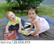 Купить «Две маленькие девочки играют с книжками в саду», фото № 28654419, снято 28 июня 2018 г. (c) Ирина Борсученко / Фотобанк Лори