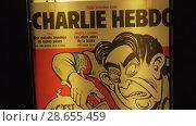 Купить «Street banner of Charlie Hebdo satirical magazine in night Paris, France», видеоролик № 28655459, снято 29 сентября 2017 г. (c) Данил Руденко / Фотобанк Лори