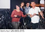 Купить «Employee helping family select bikes», фото № 28665015, снято 16 октября 2018 г. (c) Яков Филимонов / Фотобанк Лори
