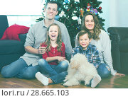 Купить «Family members preparing for photo with Christmas tree», фото № 28665103, снято 23 января 2019 г. (c) Яков Филимонов / Фотобанк Лори