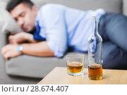 Купить «bottle of alcohol on table and sleeping drunk man», фото № 28674407, снято 24 ноября 2017 г. (c) Syda Productions / Фотобанк Лори