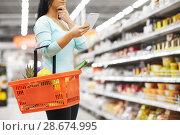 Купить «woman with food in shopping basket at supermarket», фото № 28674995, снято 2 ноября 2016 г. (c) Syda Productions / Фотобанк Лори