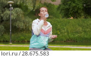 Купить «woman drinking water after exercising in park», видеоролик № 28675583, снято 25 июня 2018 г. (c) Syda Productions / Фотобанк Лори