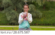Купить «woman drinking smoothie after exercising in park», видеоролик № 28675587, снято 25 июня 2018 г. (c) Syda Productions / Фотобанк Лори