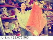 Купить «Happy woman customer choosing colored carpet», фото № 28675963, снято 22 ноября 2017 г. (c) Яков Филимонов / Фотобанк Лори