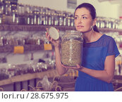 Купить «adult female take a smell natural dried herbs sold by weight in eco shop», фото № 28675975, снято 13 июня 2017 г. (c) Яков Филимонов / Фотобанк Лори