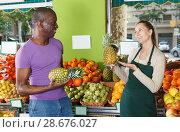 Купить «Happy seller is helping male choose pineapple», фото № 28676027, снято 26 мая 2018 г. (c) Яков Филимонов / Фотобанк Лори