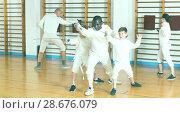 Купить «Focused boys fencers attentively listening to professional fencing coach in gym», фото № 28676079, снято 30 мая 2018 г. (c) Яков Филимонов / Фотобанк Лори