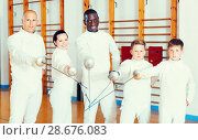 Купить «Group portrait of young fencers with coaches holding rapiers in training room», фото № 28676083, снято 30 мая 2018 г. (c) Яков Филимонов / Фотобанк Лори