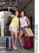 Купить «Cheerful female friends are standing with baggage and taking selfie», фото № 28683235, снято 29 мая 2017 г. (c) Яков Филимонов / Фотобанк Лори