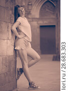 Купить «Young woman standing near old stone wall», фото № 28683303, снято 15 августа 2017 г. (c) Яков Филимонов / Фотобанк Лори