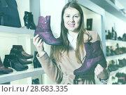 Купить «Young smiling female is demonstraiting modern ankle boots», фото № 28683335, снято 13 декабря 2017 г. (c) Яков Филимонов / Фотобанк Лори