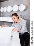Купить «Positive girl customer buying ceramic bath in store», фото № 28683383, снято 2 февраля 2018 г. (c) Яков Филимонов / Фотобанк Лори