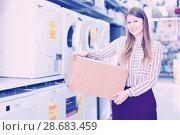 Купить «Female housewife happy from buyings in home appliance store, standing with big box», фото № 28683459, снято 12 декабря 2017 г. (c) Яков Филимонов / Фотобанк Лори