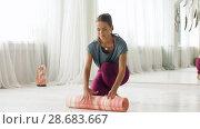 Купить «woman rolling up mat at yoga studio or gym», видеоролик № 28683667, снято 28 июня 2018 г. (c) Syda Productions / Фотобанк Лори