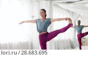 Купить «woman doing yoga hand-to-big-toe pose at studio», видеоролик № 28683695, снято 28 июня 2018 г. (c) Syda Productions / Фотобанк Лори