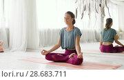 Купить «woman meditating in lotus pose at yoga studio», видеоролик № 28683711, снято 28 июня 2018 г. (c) Syda Productions / Фотобанк Лори