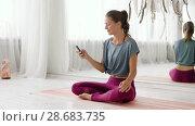 Купить «woman with smartphone at yoga studio», видеоролик № 28683735, снято 28 июня 2018 г. (c) Syda Productions / Фотобанк Лори