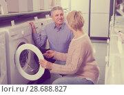 Купить «friendly mature couple chooses washing machine for their house in shop of household appliances», фото № 28688827, снято 27 марта 2019 г. (c) Яков Филимонов / Фотобанк Лори