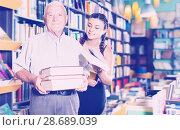 Купить «Glad grandfather with girl are choosing books», фото № 28689039, снято 28 июня 2017 г. (c) Яков Филимонов / Фотобанк Лори