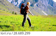 Купить «Hiking man walking on green mountain meadow with backpack. Summer sport and recreation concept.», видеоролик № 28689299, снято 17 апреля 2018 г. (c) Александр Маркин / Фотобанк Лори