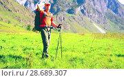 Купить «Hiking man walking on green mountain meadow with backpack. Summer sport and recreation concept.», видеоролик № 28689307, снято 23 апреля 2018 г. (c) Александр Маркин / Фотобанк Лори