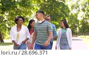 Купить «happy international friends walking in park», видеоролик № 28696371, снято 25 июня 2018 г. (c) Syda Productions / Фотобанк Лори