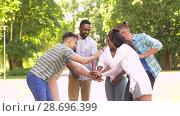 happy friends stacking hands in park. Стоковое видео, видеограф Syda Productions / Фотобанк Лори