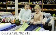 Купить «Polite female seller helping young woman in choice of interesting cloth in textile shop», видеоролик № 28702715, снято 28 марта 2018 г. (c) Яков Филимонов / Фотобанк Лори